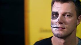 O partido de Dia das Bruxas, close-up, artista de composição tira uma composição terrível na cara de um homem para um partido de  video estoque