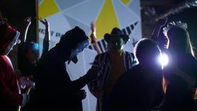 O partido de Dia das Bruxas, disco, jovens está dançando, todos é vestido em trajes assustadores para Dia das Bruxas No fundo video estoque