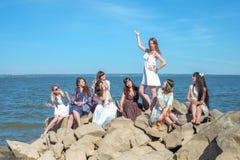 O partido do ` das meninas na praia Oito jovens mulheres perto do mar Fotos de Stock Royalty Free