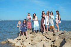 O partido do ` das meninas na praia Oito jovens mulheres perto do mar Fotografia de Stock
