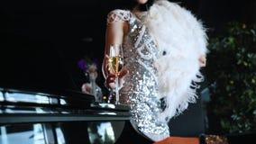 O partido do tema - um homem que joga o piano - uma mulher em cintila roupa para pegarar um vidro do champanhe video estoque