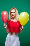 O party girl em vidros elegantes é fazendo caretas e de vista a câmera que guarda balões de ar amarelos e vermelhos no Fotos de Stock Royalty Free
