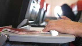 O passageiro com passaporte ench-se-er nos cartões da migração ou de chegada no voo plano do quando imagem de stock
