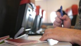 O passageiro com passaporte ench-se-er nos cartões da migração ou de chegada no voo plano do quando imagens de stock