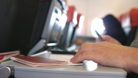 O passageiro com passaporte ench-se-er nos cartões da migração ou de chegada no voo plano do quando imagens de stock royalty free