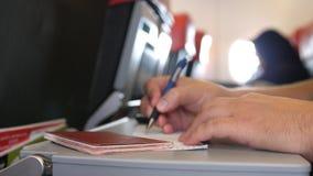 O passageiro com passaporte ench-se-er nos cartões da migração ou de chegada no voo plano do quando fotos de stock
