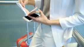 O passageiro em um terno branco verifica os originais e guardar um telefone filme