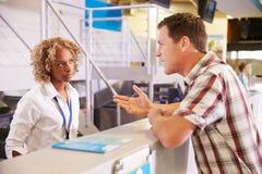 O passageiro irritado que queixa-se ao pessoal no aeroporto verifica dentro Imagens de Stock Royalty Free