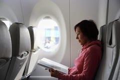 O passageiro lê um compartimento nos aviões imagem de stock