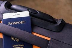 O passaporte dos E.U. e um embarque passam sobre uma mala de viagem Fotos de Stock