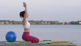 O passatempo da ioga, iogue atrativo novo fêmea na posição de lótus medita e deleita calmnes espirituais perto da água vídeos de arquivo