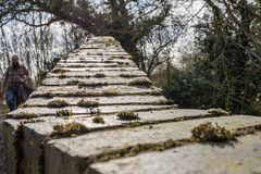 O passeio considerado do homem adulto sobre um tijolo construiu o passadiço que mede um rio pequeno imagens de stock