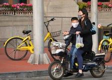 O passeio da mulher e do menino motorizou a bicicleta em Shanghai Fotografia de Stock