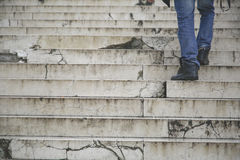 O passeio do homem escala acima em escadas velhas Fotografia de Stock