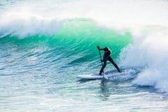 O passeio do surfista levanta-se sobre a placa de pá na onda grande do oceano Levante-se o embarque da pá no oceano foto de stock royalty free