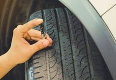 O passo de medição veste em um pneu em um carro Cofre forte a usar-se em um b diário foto de stock