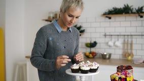 O pasteleiro fêmea em sua cozinha com auto fez queques e bolos Pastelaria decorada extravagante na tabela Movimento lento filme