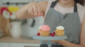 O pasteleiro polvilha bolos com a decoração e decora-os com bagas, vídeos de arquivo