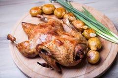 O pato cozeu inteiro, com batatas e alho Fotografia de Stock