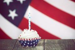 4o patriótico do queque de julho com uma vela Fotos de Stock Royalty Free