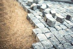 O pavimento de pedra, trabalhador da construção que coloca a pedra balança na areia Foto de Stock