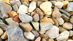 O pavimento rochoso velho do cascalho natural, seca pedras arredondadas, materiais de construção tradicionais, seixos coloridos p vídeos de arquivo