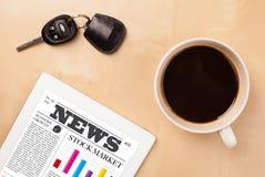 O PC da tabuleta mostra a notícia na tela com uma xícara de café em uma mesa Fotos de Stock Royalty Free