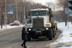 O pedestre com telefone cruza a estrada antes do caminhão fotos de stock royalty free