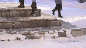O pedestre escala as escadas polvilhadas com o reagente antiderrapante contra a crosta de gelo video estoque