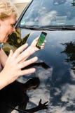 O pedestre que está sendo batido pelo carro ao jogar Pokemon vai em seu smartphone Imagens de Stock Royalty Free
