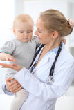 O pediatra está tomando do paciente no hospital O doutor fêmea guarda a menina da criança nas mãos Imagem de Stock