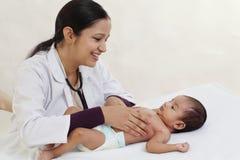 O pediatra fêmea guarda o bebê recém-nascido imagens de stock