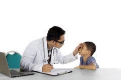 O pediatra masculino está verificando seus olhos pacientes Imagem de Stock Royalty Free