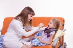 O pediatra olha a garganta de uma criança doente Fotografia de Stock Royalty Free