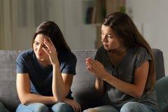 O pedido do amigo perdoa na noite em casa fotografia de stock royalty free