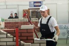 O pedreiro novo executa uma tarefa da competição Foto de Stock Royalty Free