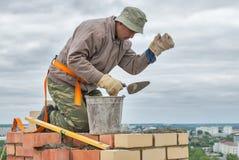 O pedreiro trabalha no 15o assoalho da construção Foto de Stock Royalty Free
