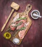 O peito de frango apetitoso bruto com alecrins, a manteiga e o sal na placa de corte do vintage martelam para a carne que o alime Fotos de Stock Royalty Free