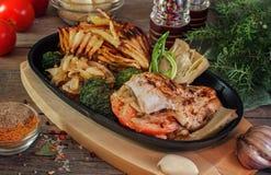 O peito de frango com cebolas, alcachofra, brócolis, fritou batatas em uma frigideira na vila fotografia de stock royalty free