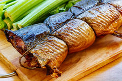 O peixe fumado em uma placa de corte com aipo desengaça Foto de Stock Royalty Free