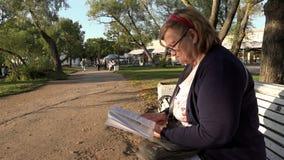 O pensionista lê com cuidado livros em um banco de parque na estação ensolarada video estoque