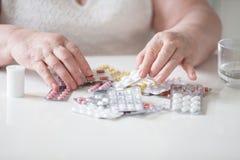 O pensionista toma seus comprimidos com suas mãos imagem de stock