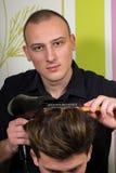O penteado dos homens e haircutting com tosquiadeira de cabelo e scissor foto de stock