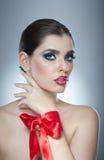 O penteado e compõe - o retrato fêmea bonito da arte com fita vermelha elegance Morena natural genuína com fita - estúdio fotografia de stock