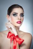 O penteado e compõe - o retrato fêmea bonito da arte com fita vermelha elegance Morena natural genuína com fita - estúdio fotografia de stock royalty free