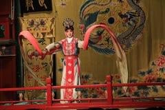 O Pequim Opera, na fase um guerreiro fêmea dança em um terno tradicional brilhante Fotografia de Stock Royalty Free