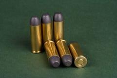 O período ocidental selvagem dos cartuchos do revólver no fundo verde Fotografia de Stock