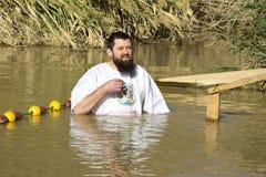O peregrino de meia idade do homem passa no rio Jordan Baptism em Jordânia imagens de stock royalty free