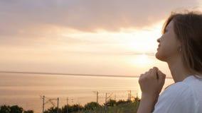 O perfil da cara da mulher bonita nova que gerencie para o deus na natureza no por do sol, rezar da menina dobrou suas mãos no qu vídeos de arquivo