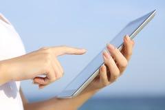 O perfil de uma mulher entrega guardar e consultar uma tabuleta digital na praia Fotos de Stock Royalty Free